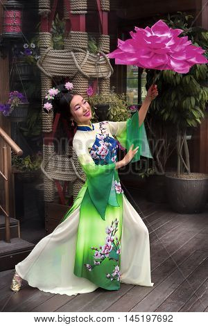 full length chinese woman in a tradition dress dancing with floral parasol