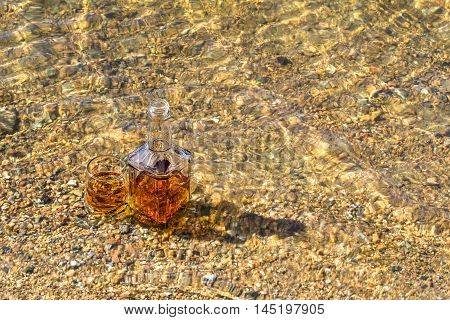Bottle and a glass of whiskey are cooled in a mountain river