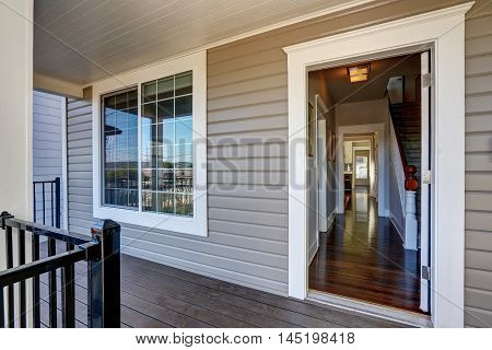 Empty Covered Porch With Open Door And French Window.