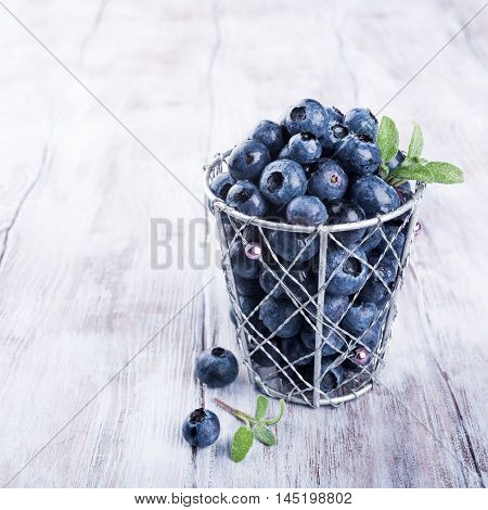 Blueberry antioxidant organic superfood in metallic cup on old white wooden background, concept for healthy eating and nutrition with copy space.