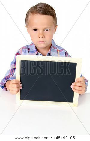 Sad five year old boy with a blank chalkboard. Add your own text.