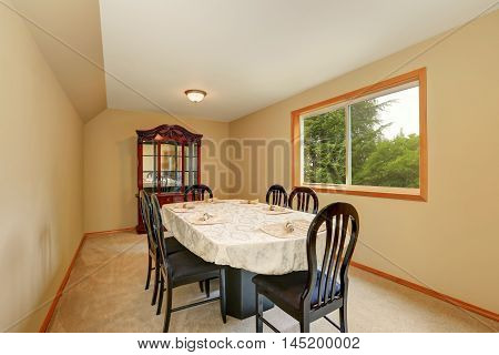 Beige Long Dining Room Interior With Black Table Set.