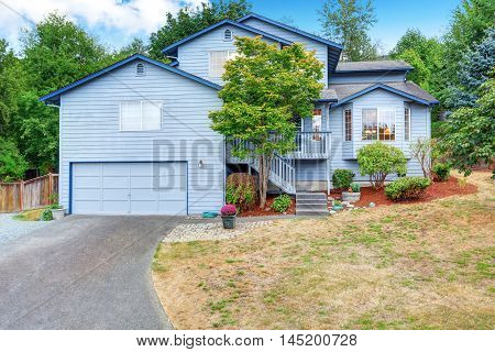 Large Blue House Exterior With Garage And Driveway