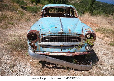 Old Abandoned Rusted Car Stands In Summer