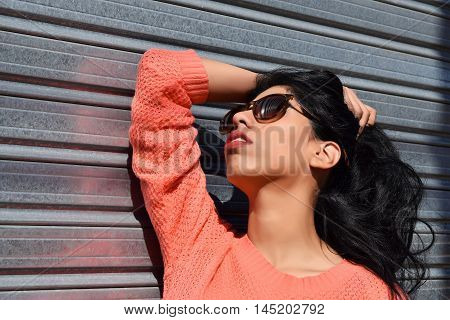Young latin woman posing outdoors. Trendy and urban style. Model posing in casual clothes.