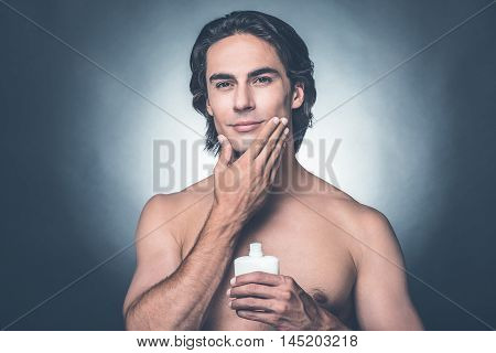 Feeling fresh after shaving. Portrait of handsome young shirtless man looking at camera and applying aftershave lotion on face while standing against grey background