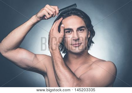 Everything should be perfect. Portrait of young shirtless man combing his hair with hairbrush and looking at camera while standing against grey background