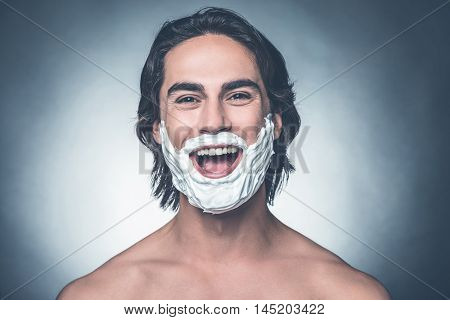 Shaving is fun. Portrait of young shirtless man with shaving cream on face looking at camera and smiling while standing against grey background