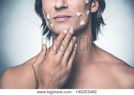 Really bad shave. Close-up of frustrated young shirtless man touching his face and expressing negativity while standing against grey background