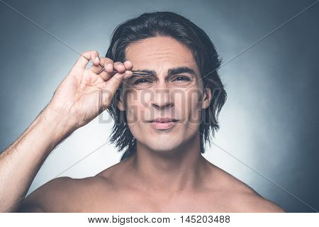 This is painful. Portrait of young shirtless man tweezing eyebrows and expressing negativity while standing against grey background