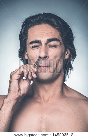 Painful procedure. Young shirtless man plucking his hair from nose and grimacing while standing against grey background