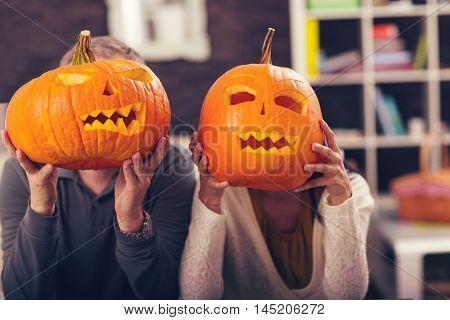 Man and woman having fun with Halloween pumpkin