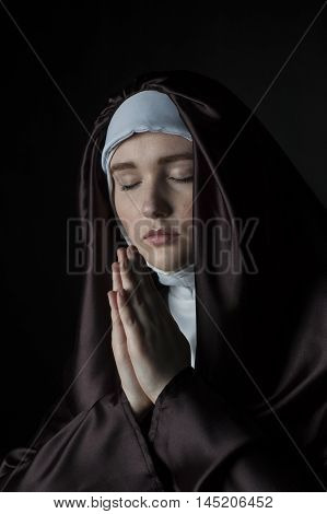 Young nun prays. Photo on black background. Low key lighting.