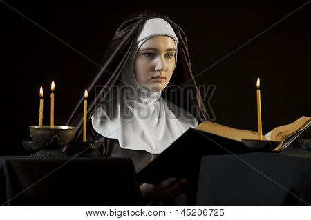 Young beautiful woman nun reading bible on black background. Through the candles. Low-key lighting.