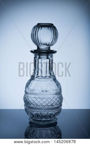 Small decanter glass on a background with gray gradient