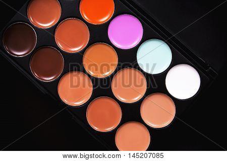 Palette concealer and correctors. Make-up base. Isolated on black background