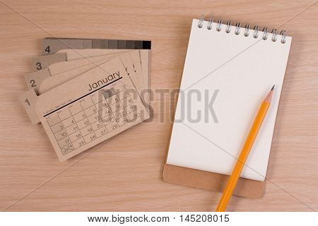 Blank business agendar on business table. Calendar and pencil on wooden table.