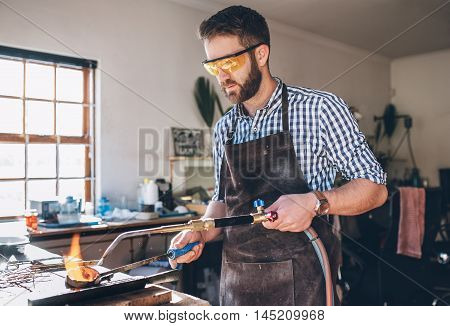 Focused jeweler using  a torch to melt metal in a crucible while working in his jewelry design studio