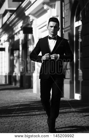 Man young handsome elegant unbuttons suit coat with bow tie outdoor black and white on urban background