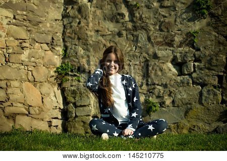 Beautiful young girl pose near medieval castle with stony wall on green grass sunny day.