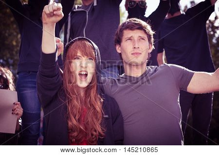 Young couple at a protest march chanting slogans with raised fists