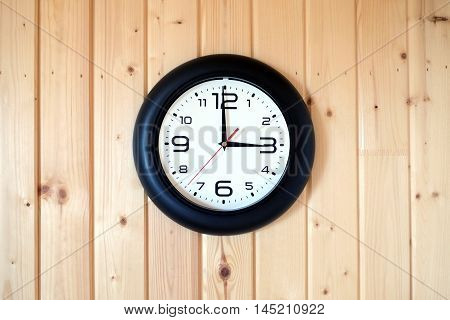Big round wall clock with a black rim with arrows showing three o'clock hangs on brown wooden wall from vertical planks horizontal view indoor on wooden background
