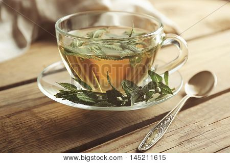 Cup of sage tea on wooden background