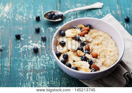 Bowl of oatmeal porridge with banana, blueberries, almonds, coconut and caramel sauce on teal vintage table. Hot and healthy food for Breakfast.