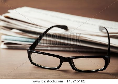 Eyeglasses and stack of newspapers on wooden desk for themes of ophthalmology, poor vision and reading.