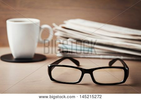 Eyeglasses, coffee mug and stack of newspapers on wooden desk for themes of ophthalmology, poor vision and reading.