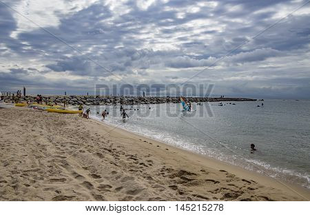 BARCELONA SPAIN - JULY 13 2016: People prepare yachts for surfing. Municipal Nautical Barcelona - surfing club for children and adult. Located in Park Poblenou Barcelona Spain.