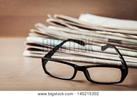 Eyeglasses and stack of newspapers on wooden desk. Ophthalmology, poor vision and reading concept.