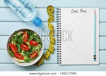 Diet plan, menu or program, tape measure, water and diet food of fresh salad on blue background. Weight loss and detox concept, top view. Flat lay.