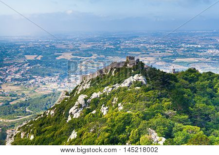 The Castle of the Moors is a hilltop medieval castle in Sintra. View of the castle from the palace of Pena. Portugal.