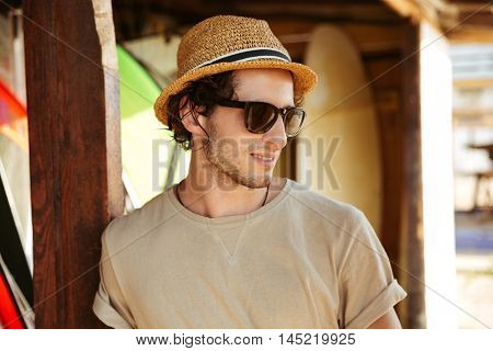 Close up portrait of a young man in sunglasses and hat standing at the surf shack