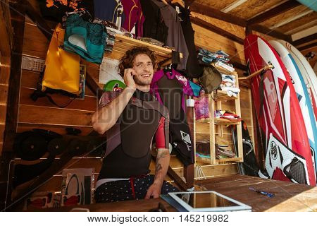Smiling young man in swimsuit talking on smartphone while sitting in the surf shack