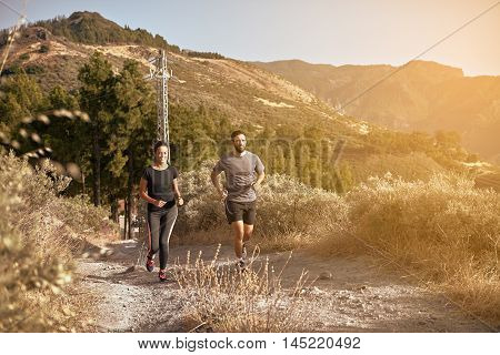 Young Couple Jogging In The Mountains