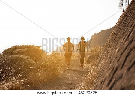 Young Couple Running Down A Mountain