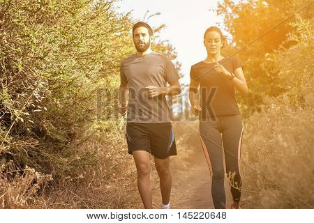 Young Friends Jogging Down A Path
