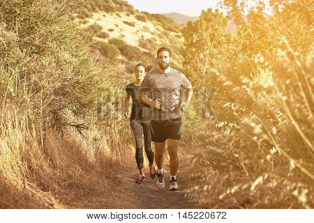 Young Couple Running Up Gravel Path