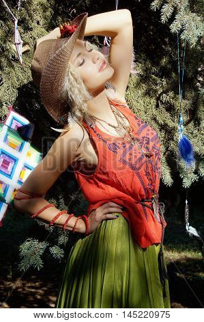 girl with blond hair in a clothes in boho style and cowboy straw hat
