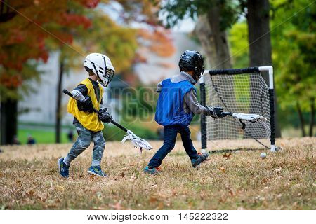 Active little kids playing lacrosse in forest camp