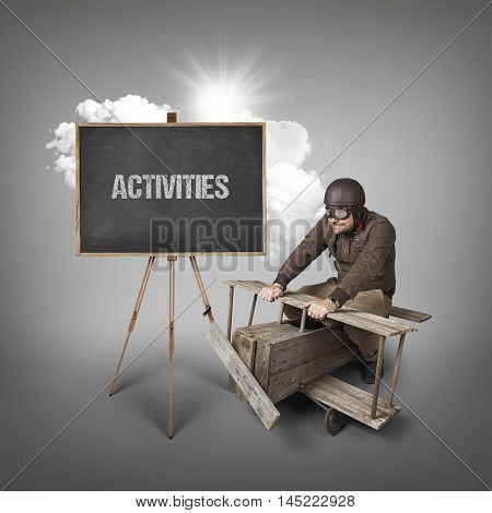 Activities text on blackboard with businessman and wooden aeroplane