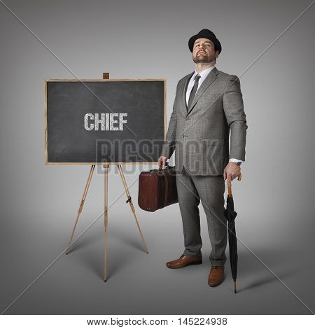 Chief text on  blackboard with businessman holding umbrella and suitcase