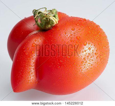 strange shaped red wet tomato in light grey back