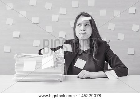 Working woman are boring from pile of hard work and work paper in front of her in work concept on blurred wooden desk and wooden wall textured background in meeting room in black and white tone