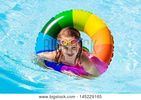 Happy little girl playing with colorful inflatable ring in outdoor swimming pool on hot summer day. Kids learn to swim. Children wearing sun protection rash guard relaxing in tropical resort