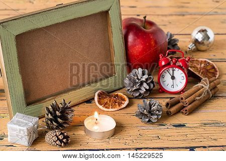 Preparing for Christmas. Christmas ornaments, pine cones, candle, clock, apple and an old photo frame on a wooden table.
