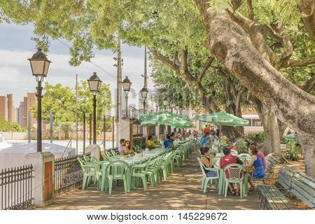 FORTALEZA, BRAZIL, DECEMBER - 2015 - People at outdoor restaurant at Martyrs square or passeio publico the most ancient public square in Fortaleza Brazil