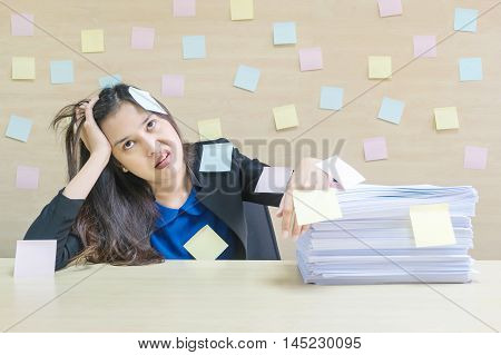 Closeup working woman are boring from pile of hard work and work paper in front of her in work concept on blurred wooden desk and wooden wall textured background in the meeting room